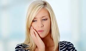blond-haired young woman suffering from dental pain