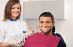 Patient in a dental chair and a standing dentist